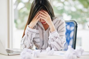Stressed woman unable to write paper